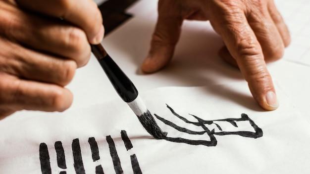 Nahaufnahme des mannes, der chinesische symbole auf weißem papier schreibt