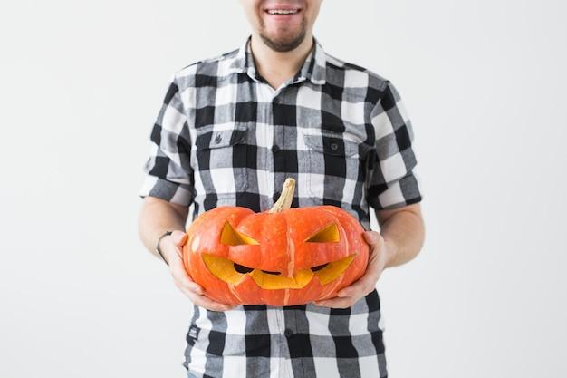 Nahaufnahme des mannes, der einen geschnitzten halloween-kürbis der jack o laterne im hellen raum hält