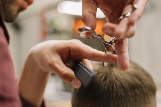 Nahaufnahme des mannes, der einen haarschnitt erhält