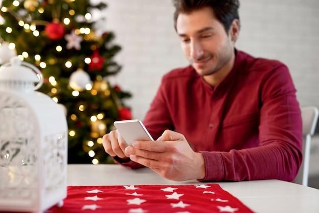 Nahaufnahme des mannes, der handy an weihnachten benutzt