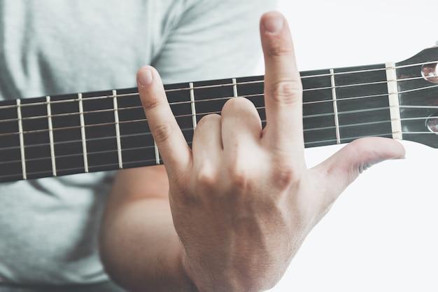 Nahaufnahme des mannes, der hornzeichen auf gitarrengriffbrett zeigt.