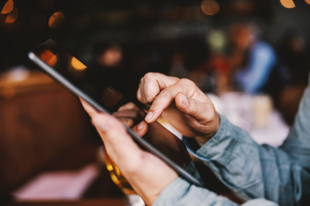 Nahaufnahme des mannes, der in einer bar sitzt und tablette verwendet