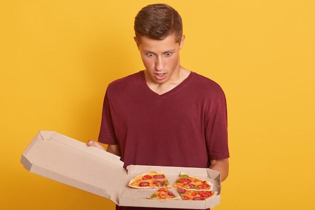 Nahaufnahme des mannes, der pizza mit geöffnetem mund und erstauntem gesichtsausdruck betrachtet