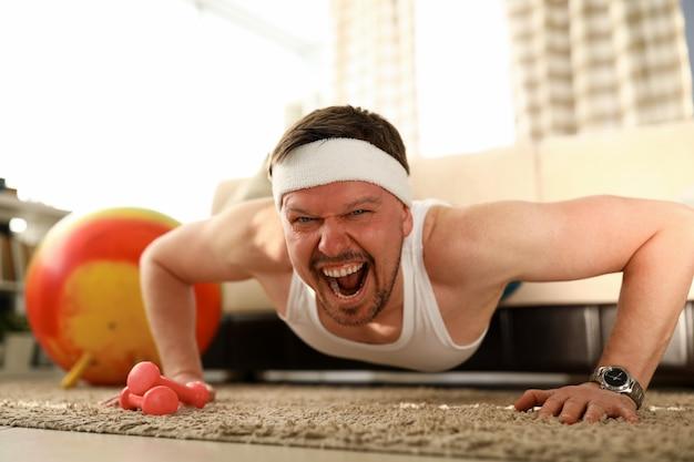 Nahaufnahme des mannes, der trainiert und nach oben drückt. körpergewichtskontrolle zu hause, sportlicher charakter im haus