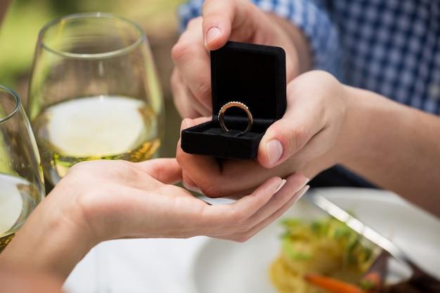 Nahaufnahme des mannes, der verlobungsring zur frau am restaurant im freien gibt