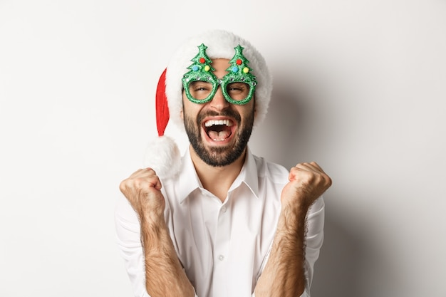 Nahaufnahme des mannes, der weihnachten oder neujahr feiert, weihnachtsfestgläser und weihnachtsmütze trägt, sich freut und freude schreit, stehend