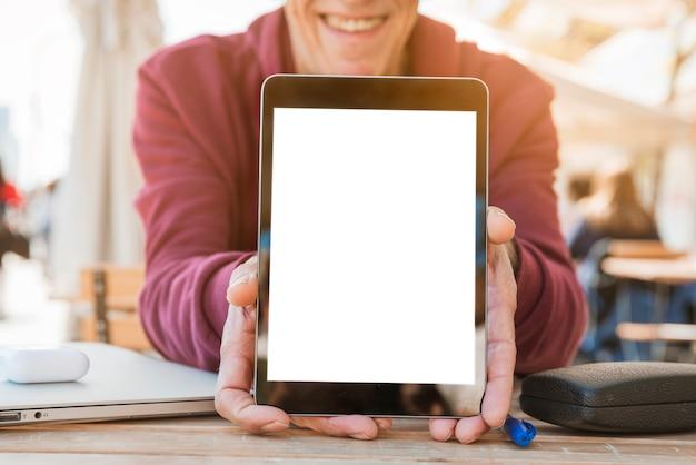 Nahaufnahme des mannes digitale tablette mit leerem weißem schirm auf holztisch zeigend
