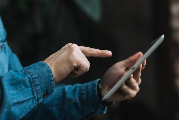Nahaufnahme des mannes finger über der digitalen tablette zeigend