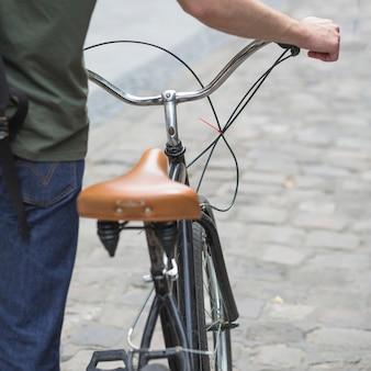 Nahaufnahme des mannes gehend mit seinem fahrrad