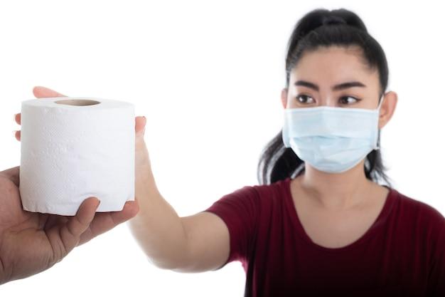 Nahaufnahme des mannes hand geben toilettenpapier einer jungen asiatischen frau auf weißem hintergrund