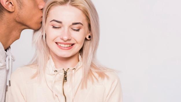 Nahaufnahme des mannes ihre lächelnde freundin gegen weißen hintergrund küssend