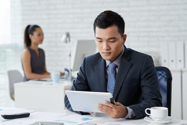 Nahaufnahme des mannes im formalwear, das am schreibtisch sitzt und am tablet-pc arbeitet