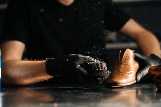 Nahaufnahme des mannes in schwarzen latexhandschuhen, die schuhbürste reinigen und staub und schmutz mit dem finger abbürsten