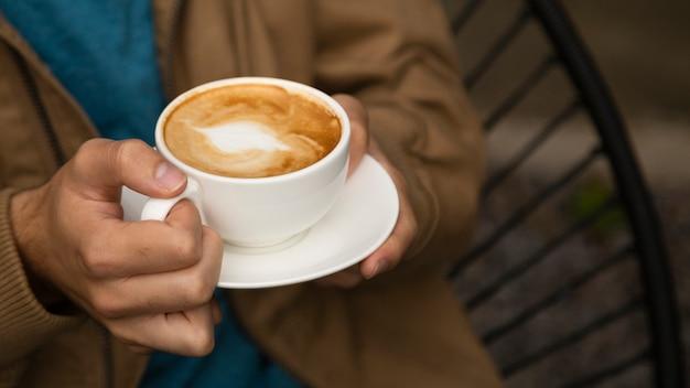 Nahaufnahme des mannes kaffeetasse halten