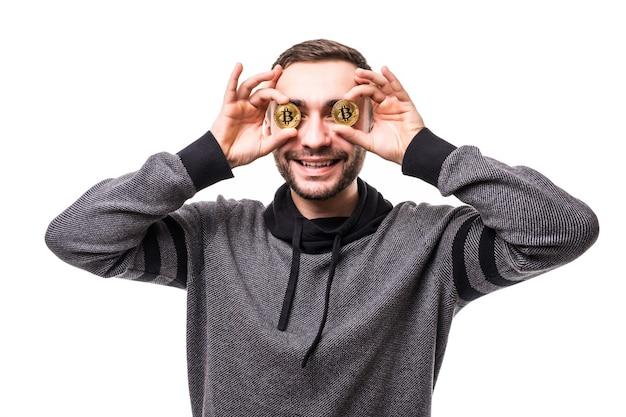 Nahaufnahme des mannes mit bitcoins in seinen augen, die finger zeigen, die über weiß isoliert sind