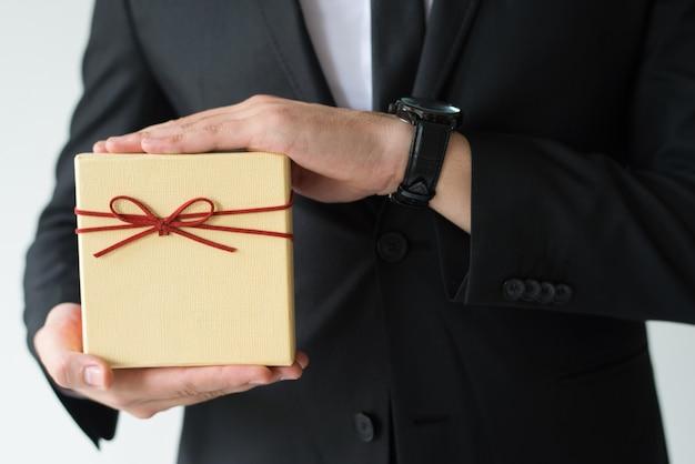 Nahaufnahme des mannes mit der armbanduhr, die geschenkbox hält