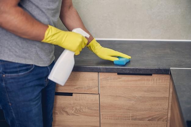 Nahaufnahme des mannes mit gelben handschuhen mit waschmittel und gummi in der küche