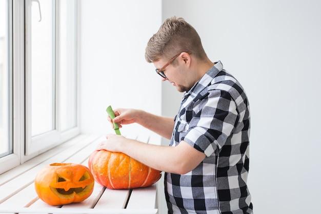 Nahaufnahme des mannes mit kürbissen, die halloween vorbereiten
