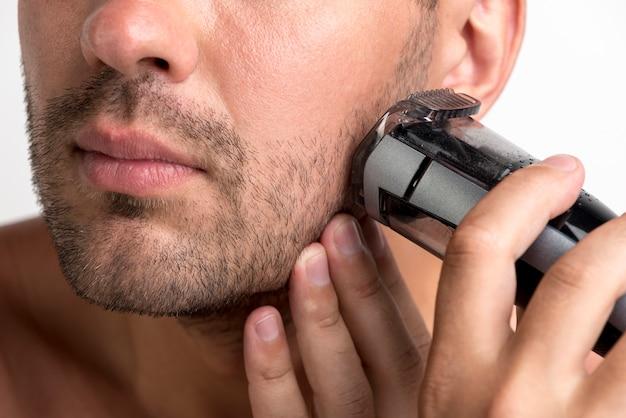 Nahaufnahme des mannes rasierend mit schwarzem trimmer