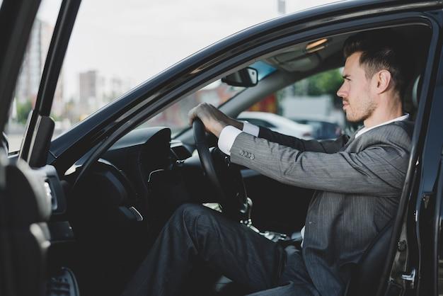 Nahaufnahme des mannes sitzend im auto, das lenkrad hält