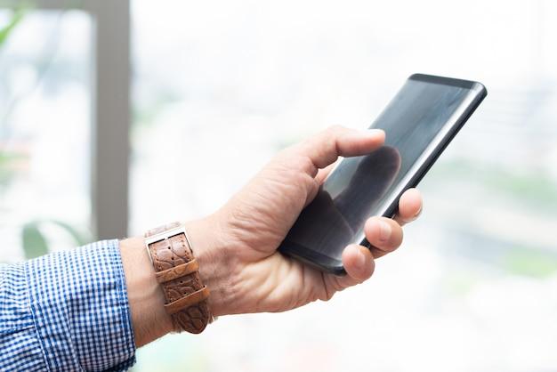 Nahaufnahme des mannes smartphone halten und auf seinem schirm klopfen