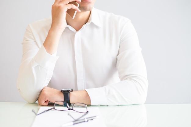 Nahaufnahme des mannes um smartphone im büro ersuchend