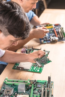 Nahaufnahme des mannes zwei it-techniker, der den stromkreis auf computer mainboard einfügt
