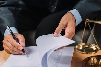 Nahaufnahme des männlichen Rechtsanwalts das Vertragsdokument auf dem Schreibtisch unterzeichnend