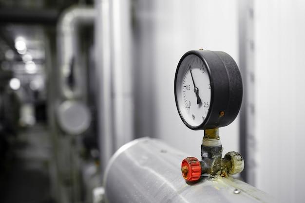 Nahaufnahme des manometers an der rohrleitung im heizwerk.