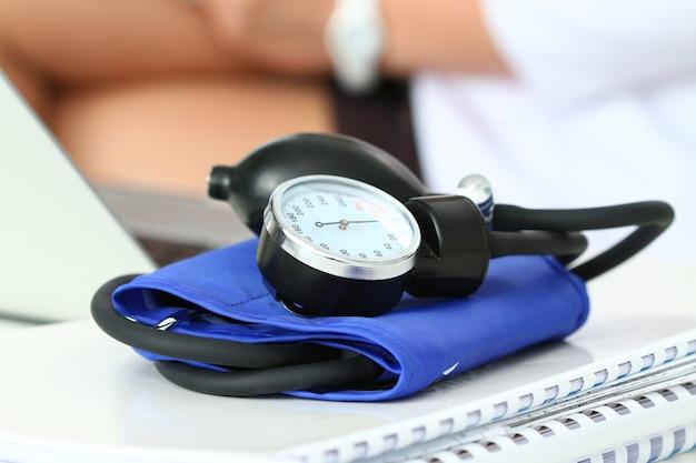 Nahaufnahme des manometers, das auf arbeitstisch liegt. krankenhausarbeitsbereich. konzept für gesundheitswesen, medizinische versorgung, behandlung, hypotonie oder bluthochdruck.