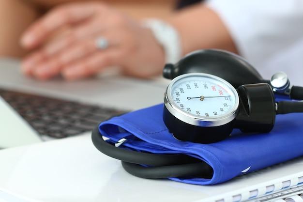 Nahaufnahme des manometers, das auf arbeitstisch liegt. krankenhausarbeitsbereich. konzept für gesundheitswesen, medizinische versorgung, behandlung, hypotonie oder bluthochdruck