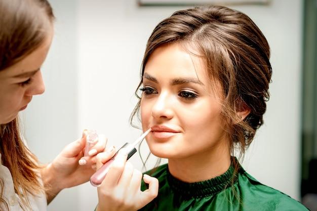 Nahaufnahme des maskenbildners, der lippenstift mit einem make-up-pinsel auf lippen der schönen jungen frau anwendet