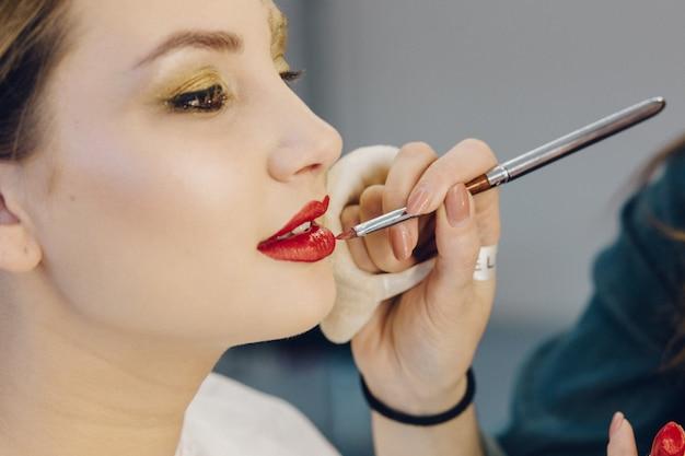Nahaufnahme des maskenbildners, der roten lippenstift auf modelllippen anwendet