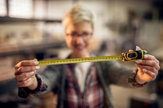 Nahaufnahme des maßbandes beim halten durch unscharfe kurzhaararbeiterin mit brille in der werkstatt