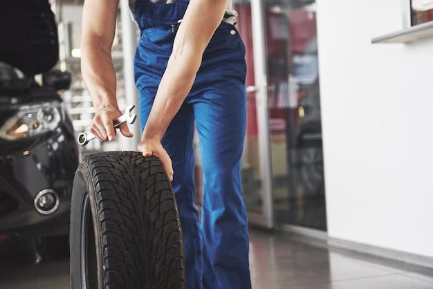 Nahaufnahme des mechanikers, der mit seinem daumen eine gute geste zeigt, während er einen schraubenschlüssel hält.