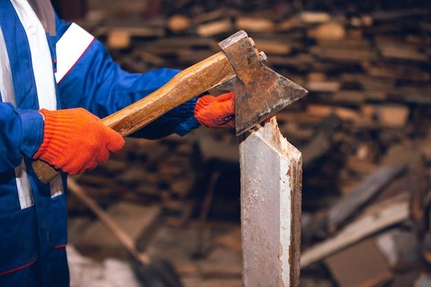 Nahaufnahme des mechanikers in uniform, professioneller baumeister, der mit baumaschinen arbeitet. bauprozess, wohnungsrenovierung, reparatur, bau. sägen, verbinden, schneiden, vorbereiten.