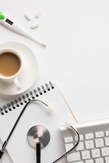 Nahaufnahme des medizinischen gesundheitspflegeschreibtischs mit kaffeetasse auf weißer oberfläche