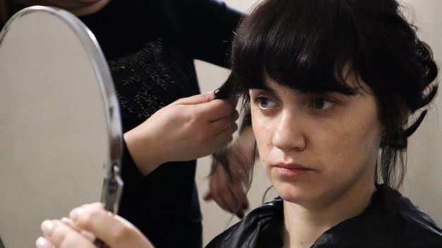 Nahaufnahme des meisterfriseurs, der zu hause lockige frisur und make-up für schöne frau mit dunklen haaren macht. hochzeitsfrisur für die braut.