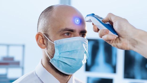 Nahaufnahme des menschen in einer schutzmaske misst die temperatur mit einem digitalen thermometer