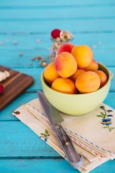 Nahaufnahme des messers und des frischen pfirsiches in der schüssel auf serviette