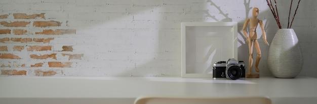 Nahaufnahme des minimalen arbeitsbereichs mit kamera, dekorationen und kopierraum auf weißem tisch