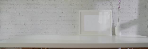 Nahaufnahme des minimalen innendesigns mit modellrahmen, keramikvase und kopierraum auf weißem tisch