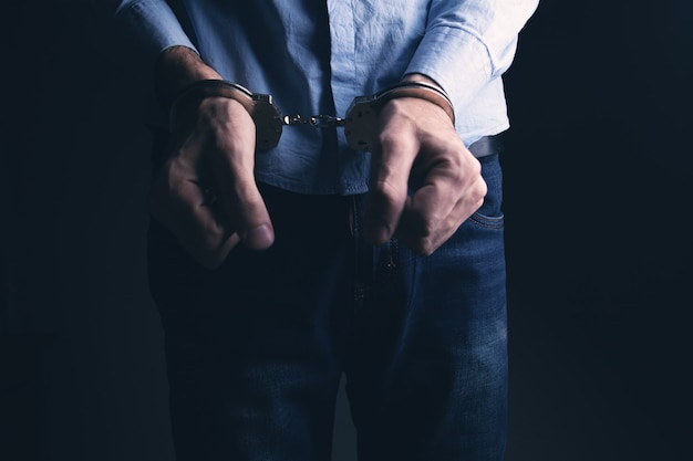 Nahaufnahme des mit handschellen gefesselten mannes