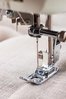 Nahaufnahme des modernen nähmaschinen-nähfußes und des nadel-nähen-kleidungsstücks.