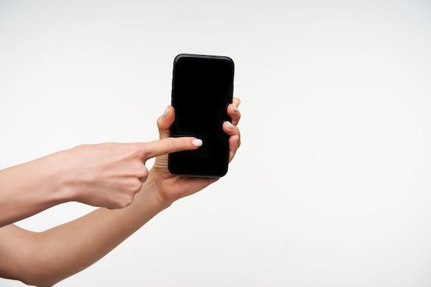 Nahaufnahme des modernen schwarzen handys, das durch die erhobene frauenhand gehalten wird und auf bildschirm mit zeigefinger wischt, während auf weiß stehend