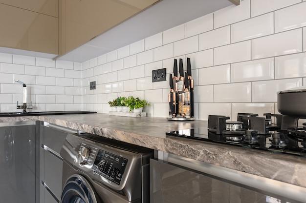 Nahaufnahme des modernen weißen, beige und grauen küchenluxusinnenraums