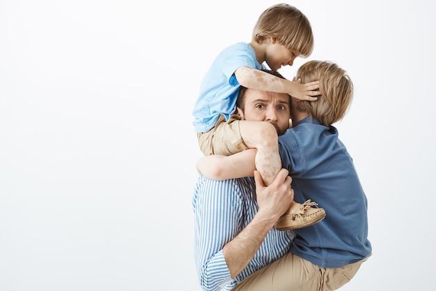 Nahaufnahme des müden besorgten vaters, der kleinen sohn auf den schultern hält, während älterer sohn an der brust hängt und vater umarmt und mit besorgtem ausdruck starrt