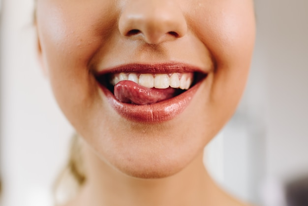 Nahaufnahme des mundes der jungen schönen kaukasischen frau, die lächelt und ihre zunge heraus hat, frech, glücklich. perfekte weiße zähne. toller hautzustand. mädchen trägt roten lippenstift.