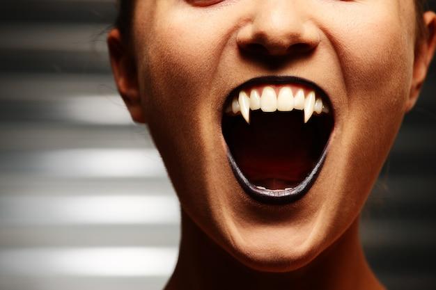 Nahaufnahme des mundes einer vampirfrau auf dunklem hintergrund