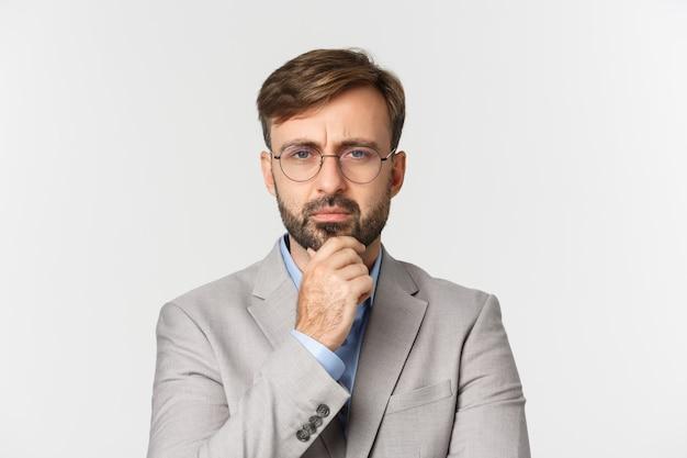 Nahaufnahme des nachdenklichen bärtigen geschäftsmannes, der brille und grauen anzug trägt